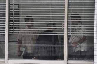 外反母趾(ぼし)の痛みが原因か、知事室から出た後、廊下で腰掛ける翁長雄志知事(中央)=27日午前9時17分ごろ、沖縄県庁