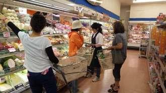 空っぽの商品棚を埋め尽くした野菜を買い求める南大東村の人たち=2日、Aコープ南大東店