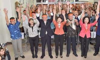 当確の報を受け、万歳で喜ぶ玉城デニー氏(前列左から3人目)=22日午後8時すぎ、沖縄市安慶田の選挙事務所