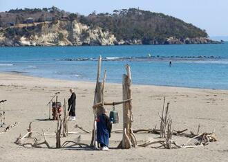 震災犠牲者の慰霊法要で、津波で流された鐘を鳴らす僧侶=2月28日午前、宮城県七ケ浜町の菖蒲田海水浴場