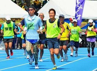 伴走者とロープをつなぎ1500メートルのスタートを切る選手たち=浦添市陸上競技場