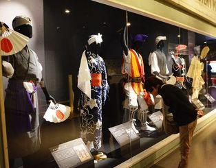 エイサーの衣装の展示に見入る来場者ら=25日、沖縄市上地・エイサー会館