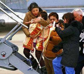 【希羽ちゃん渡米】母親に抱きかかえられ、医療用小型ジェットに乗り込む翁長希羽ちゃん。中央は父親の司さん=2016年1月、関西空港