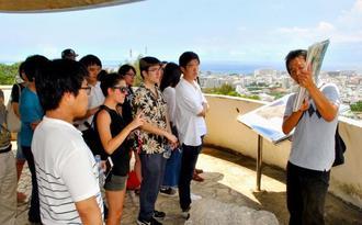 普天間飛行場を見渡せる嘉数高台から基地問題について学ぶ学生ら=7月26日、宜野湾市