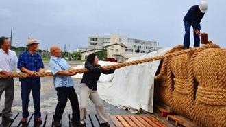 完成した綱を引く城間幹子市長(右から2人目)ら=5日、那覇軍港