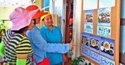 品書きを見る外国人観光客に「ウニ、ノー」と説明する菊池さん(右)。英語と中国語で「ウニ漁お休みです」と記した張り紙もしている=29日、今帰仁村古宇利島
