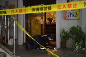 強盗が入った喫茶店入り口を調べる捜査員=19日午前3時15分ごろ、糸満市西崎