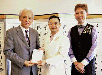 寄付金を託した大城学さん(中央)と小橋川康之さん(右)=9日、沖縄タイムス社
