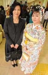 城間優子さん(左)が染めた紅型の振り袖を羽織る新成人の長女・ふみ桜さん=8日、南風原町立中央公民館