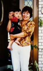 自宅玄関で孫を抱く60歳前後の安慶名静枝さん。与那城町役場を退職した後で、物忘れなどの症状が出始めていた=2005年ごろ、沖縄市(安慶名達也さん提供)