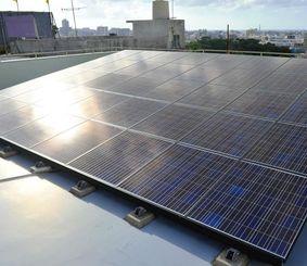 民家の屋上に設置された太陽光発電のパネル=24日、那覇市内