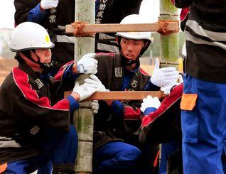 「はしご乗り」を支える高校生団員の新田圭一郎さん(中央)=石垣市消防本部