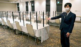 感染防止対策のためパーテンションの設置を徹底した宴会場を紹介する河野航係長=22日、那覇セントラルホテル