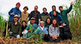 代表の林さん(後列右)ら社員総出で、定期的に糸満市にある自社の指定農園でキビを刈り取り、黒糖を作っている=糸満市豊原、2018年1月