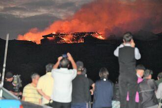 龍潭池付近から炎上する首里城を見上げる地域住民ら=31日午前6時12分、那覇市首里