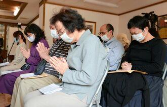 東日本大震災が発生した午後2時46分に合わせ、手を合わせる参加者ら=11日、糸満市・長谷寺