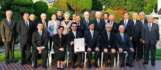 表彰状を手に、沖縄系初の表彰を関係者と喜ぶ比嘉朝儀さん(前列左から3番目)と新見潤・在ロサンゼルス総領事(同4番目)=ロサンゼルス市内の総領事公邸
