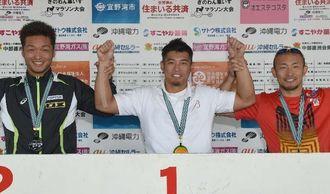 脊損の部で優勝した西田宗城さん(中央)、2位の渡辺勝さん(左)、3位の廣道純さん=14日午後、宜野湾海浜公園