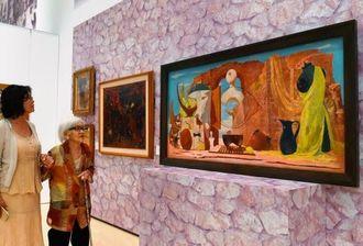 ニシムイ展で夫の故山元恵一さんの作品を鑑賞する文子さん(右)=13日、那覇市の県立博物館・美術館コレクションギャラリー