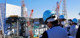 2号機(左)の廃炉に向けた作業状況の説明を受ける取材団=6日、福島県・東京電力福島第1原発(代表撮影)