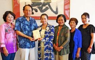 沖縄タイムス社の豊平良考社長(左から2人目)に義援金を託す健康体操結の会