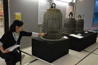 他の鐘には見られない青海波紋を指さし説明する県立博物館・美術館の崎原恭子学芸員=25日、同館