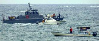 辺野古沖に浮かぶ警戒船(手前)と、航行する市民の抗議船(中央)、並走する警備会社の警備艇=5月