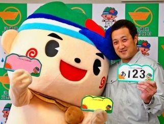 ご当地ナンバープレートをPRするぎ~のくん(左)と仲間芳博主事=25日、宜野座村役場