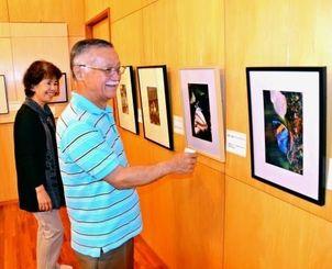 友利哲夫さんの写真展を企画した岸本明さん(右)と妻のヨシ子さん=西原町我謝の岸本さん宅