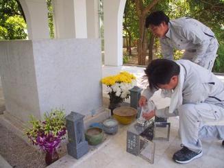ミャンマーのヤンゴン日本人墓地で、日本製の灯籠などを設置する湊賢一郎さん(手前)=8日(共同)