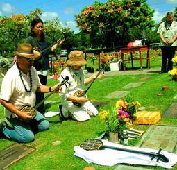 嘉数亀助さんの墓前に「里帰り三線」を供え、感謝を込めて「安里屋ユンタ」を演奏する嘉数進さん(手前左)と和子さん(同右)夫妻ら=ハワイ州ホノルル市