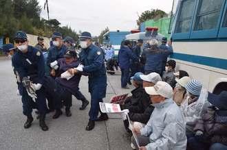 ゲート前で座り込んで抗議する市民を排除する機動隊員=10日午前9時6分、名護市辺野古・米軍キャンプ・シュワブ前