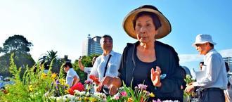 原爆死没者慰霊碑前で、一輪のガーベラを手向ける新垣和子さん=6日午前7時半ごろ、広島市・平和記念公園