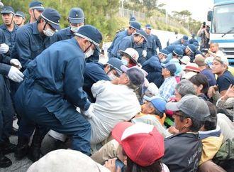 米軍キャンプ・シュワブゲート前に座り込む市民らを排除する機動隊=23日午前、名護市辺野古