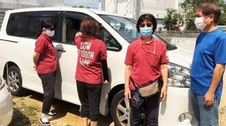 NPO法人ロービジョンライフ沖縄のスタッフと買い替えた8人乗りワゴン車=4月30日、那覇市(提供)