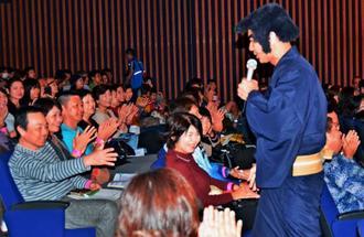 持ち歌を歌いながら場内を歩く護得久栄昇さん(右)=4日、国立劇場おきなわ