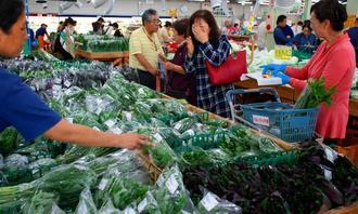 島ヤサイ専用の販売コーナーでは品定めする買い物客でにぎわった=8日、糸満市・JAファーマーズマーケットいとまん