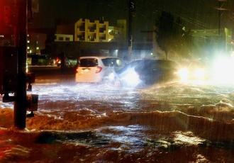 大雨で冠水し、波立つ県道38号を走る車両=19日午後9時すぎ、西原町嘉手苅(渡辺奈々撮影)