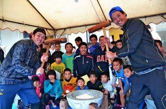 子どもたちに囲まれながら餅をつく徳山武陽投手(手前右)と由規投手(同左)=17日、浦西公民館