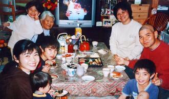 娘家族と写真に納まる知花キヨさん(左奥)。四女新川美津留さん(右奥)の夫博文さん(右)は2回目の脳腫瘍手術を受けた後だった=2005年1月、名護市(美津留さん提供)