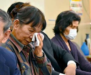 記者会見で涙を拭う祖堅秀子さん(左)=7日、県庁