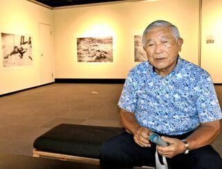 企画展に展示された写真を前に、「伊江島米軍LCT爆発事件」で父を失った悲しみを語る主和津ジミー(幸地達夫)さん=3日、那覇市民ギャラリー