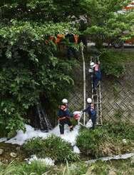 宇地泊川にたまった泡消火剤を回収する消防隊員ら=11日午前11時ごろ、宜野湾市・大謝名橋付近