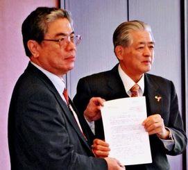 大城紀夫会長(左)からの要請書を手に取る安里会長=ロワジールホテル那覇