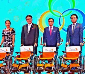 県ホテル協会の當山智士会長(右から2人目)に車いすを贈ったリアンズグループの槙山良夫CEO(同3人目)=8日、那覇市・沖縄かりゆしアーバンリゾート・ナハ