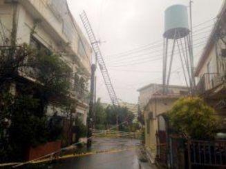 屋上の金属製の柵が壊れ、道路をふさいでいた。通行止めのテープが張られていた=10日午前7時57分、浦添市(平良秀明撮影)