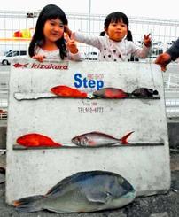 上里さんが北谷沖で釣った63センチ、4・97キロのマクブ。写真は長女の幸愛(コア)ちゃん(左)と次女の來愛(ララ)ちゃん=6日