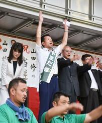 茨城県東海村の村長選で、無投票での再選が決まり万歳する山田修氏(中央)=22日午後