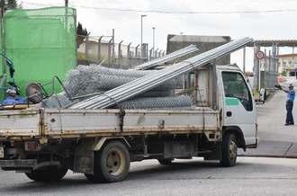 資材のようなものを積み、米軍キャンプ・シュワブに入るトラック=13日、名護市辺野古