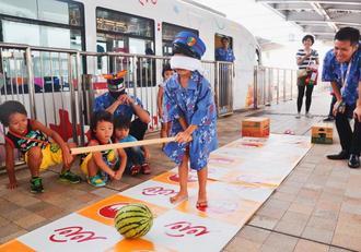 ホームでスイカ割りに挑戦する竹下陽琉(あける)さん(中央)=10日、沖縄都市モノレールの首里駅